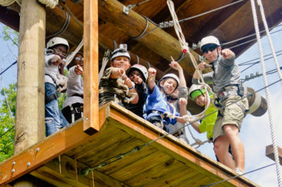 Campers on the high ropes course, where campers cheer each other on as they learn to conquer and overcome.