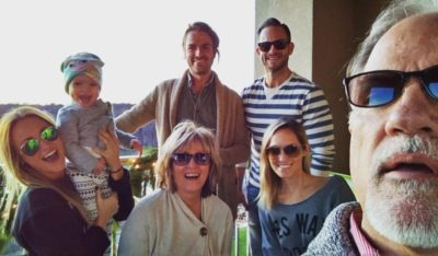 Christy, bottom right, on vacation with her parents, siblings, husband (in stripes) and daughter.
